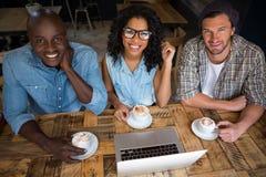 Amis heureux ayant le café avec l'ordinateur portable sur la table en café Photographie stock libre de droits