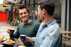 Amis heureux ayant le café ensemble Image stock