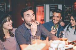 Amis heureux ayant le cocktail potable d'amusement dans une barre - jeunes à la mode riant et appréciant ensemble la vie nocturne photographie stock