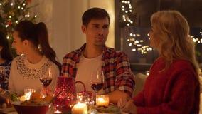 Amis heureux ayant le dîner à la maison de Noël banque de vidéos