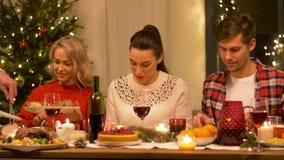 Amis heureux ayant le dîner à la maison de Noël clips vidéos