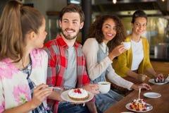 Amis heureux ayant le dessert en café Image libre de droits