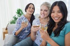 Amis heureux ayant le vin blanc regardant ensemble l'appareil-photo Image libre de droits