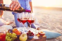 Amis heureux ayant le vin rouge sur la plage Partie de plage de coucher du soleil Photographie stock libre de droits