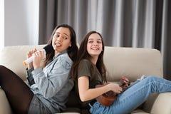 Amis heureux ayant un grand temps sur le divan dans le salon Image libre de droits
