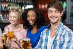 Amis heureux ayant une boisson Photographie stock libre de droits