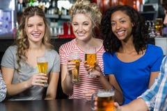 Amis heureux ayant une boisson Image stock