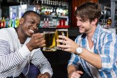 Amis heureux ayant une boisson Images stock