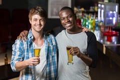 Amis heureux ayant une boisson Photos stock