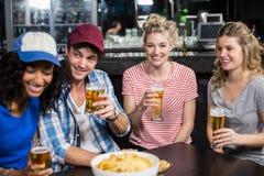 Amis heureux ayant une boisson Photos libres de droits