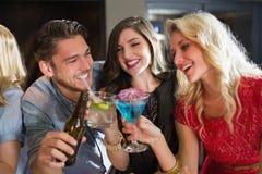 Amis heureux ayant une boisson ensemble Photographie stock libre de droits