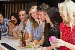 Amis heureux ayant une boisson ensemble Images stock