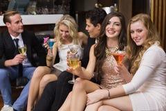 Amis heureux ayant une boisson ensemble Photos stock