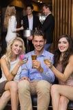 Amis heureux ayant une boisson ensemble Photo stock