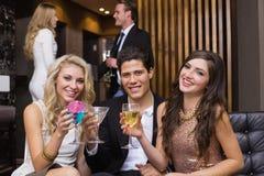 Amis heureux ayant une boisson ensemble Image stock