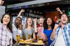 Amis heureux ayant une boisson et observant le sport Photographie stock libre de droits