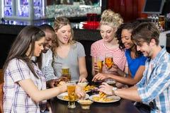 Amis heureux ayant une boisson et un hamburger Photos stock