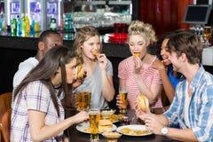 Amis heureux ayant une boisson et un hamburger Image libre de droits