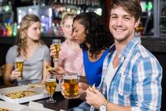 Amis heureux ayant une boisson et une pizza Images libres de droits
