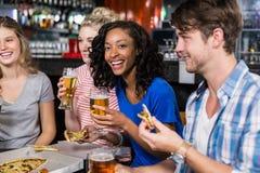 Amis heureux ayant une boisson et une pizza Image stock