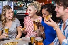 Amis heureux ayant une boisson et une pizza Images stock