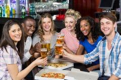 Amis heureux ayant une boisson et une pizza Photographie stock libre de droits