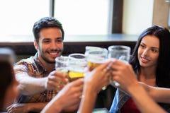Amis heureux buvant de la bière à la barre ou au bar Images stock
