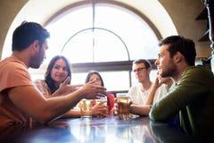 Amis heureux buvant de la bière à la barre ou au bar Images libres de droits