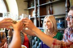 Amis heureux buvant de la bière à la barre ou au bar Photos stock