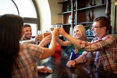 Amis heureux buvant de la bière à la barre ou au bar Image stock