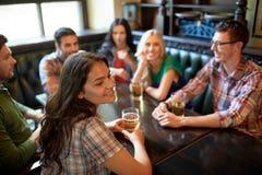 Amis heureux buvant de la bière à la barre ou au bar Photo stock