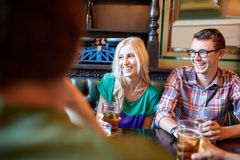 Amis heureux buvant de la bière à la barre ou au bar Image libre de droits