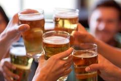 Amis heureux buvant de la bière à la barre ou au bar Photos libres de droits