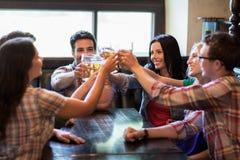 Amis heureux buvant de la bière à la barre ou au bar Photographie stock
