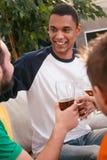 Amis heureux buvant de la bière à la maison Photos stock
