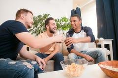 Amis heureux buvant de la bière à la maison Photo stock