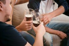 Amis heureux buvant de la bière à la maison Image stock