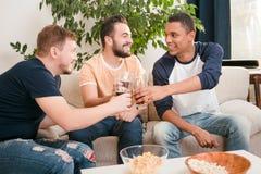 Amis heureux buvant de la bière à la maison Images libres de droits