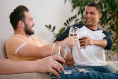 Amis heureux buvant de la bière à la maison Image libre de droits