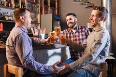Amis heureux buvant de la bière au compteur dans le bar Image stock