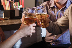 Amis heureux buvant de la bière au compteur dans le bar Photo libre de droits