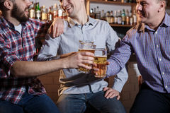 Amis heureux buvant de la bière au compteur dans le bar Photo stock