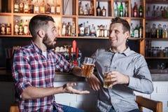Amis heureux buvant de la bière au compteur dans le bar Images stock