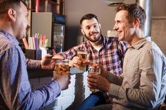 Amis heureux buvant de la bière au compteur dans le bar Photographie stock libre de droits