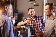 Amis heureux buvant de la bière au compteur dans le bar Photographie stock