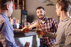 Amis heureux buvant de la bière au compteur dans le bar Photos stock
