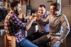 Amis heureux buvant de la bière au compteur dans le bar Images libres de droits