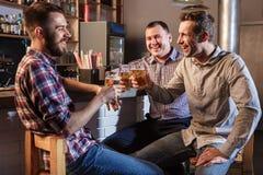 Amis heureux buvant de la bière au compteur dans le bar Photos libres de droits