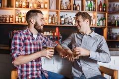 Amis heureux buvant de la bière au compteur dans le bar Image libre de droits