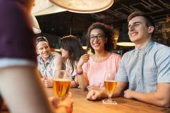 Amis heureux buvant de la bière et parlant à la barre Image stock